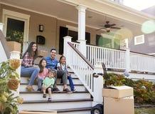 Famiglia che si siede sui punti di nuova casa sul muoversi nel giorno fotografia stock