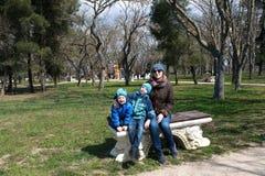Famiglia che si siede sul banco fotografie stock