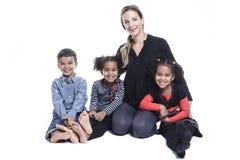 Famiglia che si siede sul pavimento di uno studio di fotografia Fotografie Stock