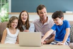 Famiglia che si siede sul sofà facendo uso del computer portatile in salone a casa Immagini Stock