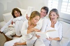 Famiglia che si siede sul sofà mentre la madre legge il libro fotografia stock libera da diritti