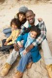 Famiglia che si siede sulla spiaggia di inverno Immagini Stock