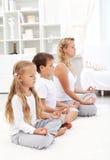 Famiglia che si siede in una riga che meditating Fotografia Stock Libera da Diritti