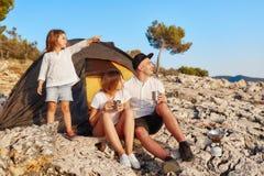 Famiglia che si siede vicino alla tenda alle vacanze estive piene d'ammirazione della spiaggia della roccia fotografia stock libera da diritti