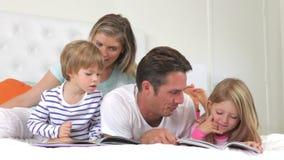 Famiglia che si trova a letto libri di lettura insieme stock footage