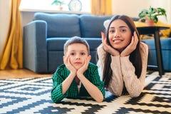 Famiglia che si trova su un tappeto nel loro salone fotografia stock