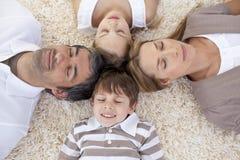 Famiglia che si trova sul pavimento nel paese con le teste insieme Immagini Stock