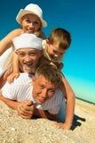 Famiglia che si trova sulla sabbia Immagini Stock