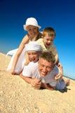 Famiglia che si trova sulla sabbia Fotografia Stock Libera da Diritti