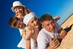 Famiglia che si trova sulla sabbia Fotografie Stock
