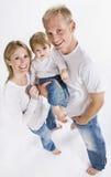 Famiglia che sorride alla macchina fotografica Immagine Stock