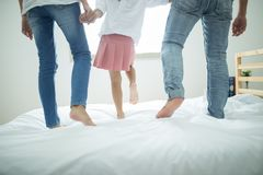 Famiglia che spende tempo libero a casa, famiglia felice che salta insieme sul letto fotografie stock libere da diritti