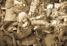 Famiglia che sta ai ricordi coniferi contro Immagini Stock