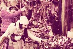 Famiglia che sta ai ricordi coniferi contro Immagine Stock