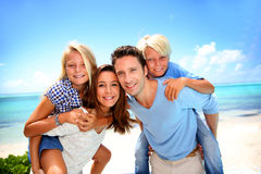 Famiglia che sta su una bella spiaggia Immagine Stock