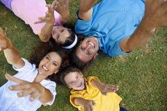 Famiglia che stabilisce le mani in su che ridono Immagini Stock Libere da Diritti