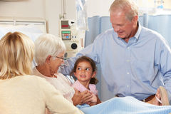 Famiglia che visualizza paziente femminile senior nel letto di ospedale Fotografia Stock Libera da Diritti