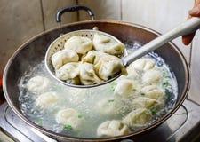 Famiglia cinese che cucina gli gnocchi bolliti in wok Fotografie Stock