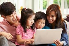 Famiglia cinese che per mezzo del computer portatile mentre distendendosi Fotografia Stock Libera da Diritti