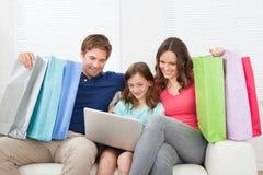 Famiglia con dei sacchetti della spesa facendo uso del computer portatile Fotografie Stock