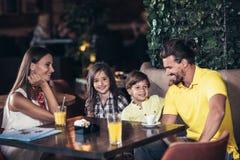 Famiglia con due bambini che hanno grande tempo in un caffè dopo shopp fotografia stock