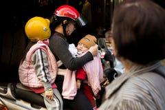 Famiglia con due bambini su un motociclo, sulla madre e sui suoi bambini immagini stock