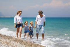 Famiglia con due bambini sulla spiaggia immagini stock libere da diritti