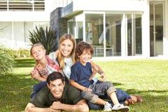Famiglia con due bambini in un giardino Immagine Stock