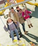 Famiglia con due ragazze divertendosi sulle oscillazioni all'aperto fotografie stock libere da diritti