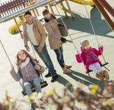 Famiglia con due ragazze divertendosi sulle oscillazioni all'aperto immagini stock