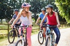 Famiglia con gli adolescenti sul giro del ciclo in campagna Immagini Stock