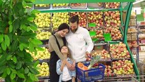 Famiglia con gli ortaggi da frutto d'acquisto del bambino nel supermercato, ritratto stock footage
