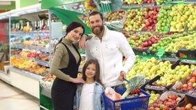 Famiglia con gli ortaggi da frutto d'acquisto del bambino nel supermercato, ritratto archivi video