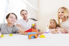 Famiglia con i bambini che costruiscono casa fotografia stock