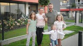 Famiglia con i bambini che esaminano macchina fotografica che sta sulla via all'aperto Coppie e bambini che comprano nuova casa P archivi video