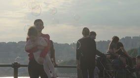 Famiglia con i bambini che fanno passeggiata su lungomare nell'ambito delle bolle di sapone, ragazza della tenuta del ragazzo video d archivio
