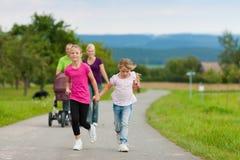 Famiglia con i bambini ed il cane che hanno camminata Fotografie Stock