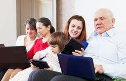 Famiglia con i computer portatili sul sofà a casa Fotografie Stock
