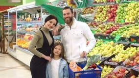 Famiglia con i frutti d'acquisto del bambino e mele nel supermercato, ritratto archivi video