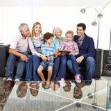 Famiglia con i nonni ed il computer della compressa immagine stock