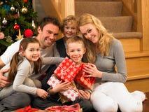 Famiglia con i regali davanti all'albero di Natale Fotografie Stock Libere da Diritti