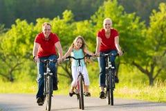 Famiglia con il bambino che cicla di estate con le biciclette fotografia stock libera da diritti