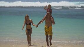 Famiglia con il bambino sulla spiaggia Immagini Stock
