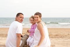Famiglia con il bambino sulla spiaggia Immagine Stock