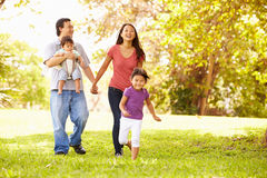 Famiglia con il bambino in trasportatore che cammina attraverso il parco fotografia stock libera da diritti