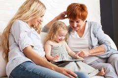 Famiglia con il computer della compressa al sofà Fotografia Stock