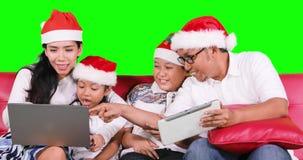 Famiglia con il computer portatile e la compressa di uso del cappello di Santa stock footage
