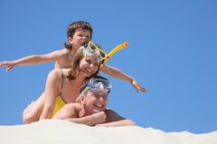 Famiglia con il figlio sulla sabbia con la mascherina navigante usando una presa d'aria Immagine Stock Libera da Diritti