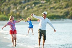 Famiglia con il piccolo bambino sulla spiaggia del mare immagine stock libera da diritti
