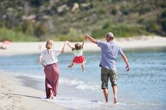 Famiglia con il piccolo bambino sulla spiaggia del mare fotografia stock